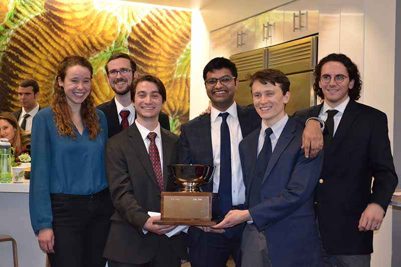 six students hold a trophy for winning a capstone project.