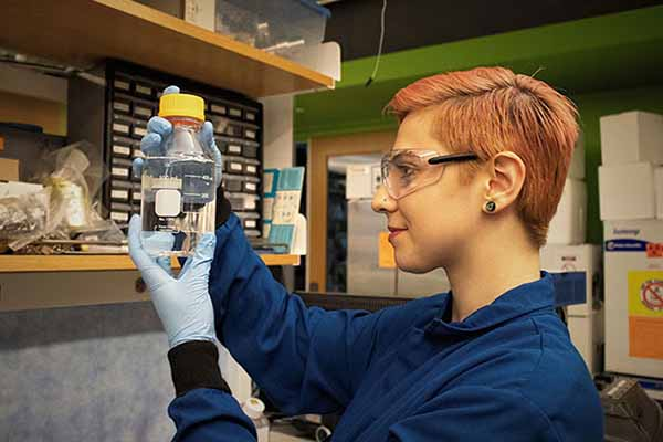 student in blue lab coat looking at chemical in bottle in lab